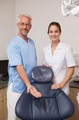 Dentist and assistant smiling at camera inviting you to the chair at the dental clinic