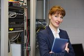 Pretty technician smiling at camera beside open server in large data center