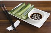 Sesame seeds in soy sauce with cucumber slices in tray and chopsticks on wooden table