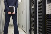 Technician standing in server hallway in large data center