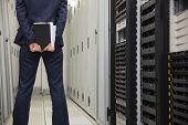 Technician standing in server hallway in large data center