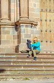 Cuzco, Peru - female tourist sitting on steps of San Francisco church