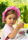 portrait of little cute girl in a purpule cap eats with appetite a breakfast from a plate with the d