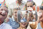 Hand holding smartphone showing happy extended family celebrating a birthday