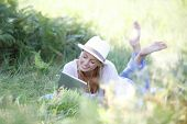Relaxed woman using digital tablet in country field