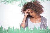 picture of pain-tree  - Sad woman holding her forehead with her hand against frost and fir trees in green - JPG