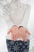 Woman standing with her hands out against snowflakes on silver