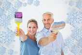 Happy couple holding paintbrushes smiling at camera against snowflake frame