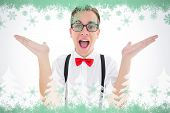 Geeky young hipster smiling at camera against green snowflake design