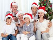 Family celebrating Christmas with wine and sweets against snow falling
