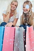 Close of bags with girls above them smiling against snow falling