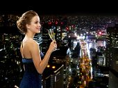 party, drinks, holidays, luxury and celebration concept - smiling woman in evening dress with glass of sparkling wine over night city background