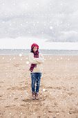 Pretty woman in stylish warm clothing at beach against snow falling