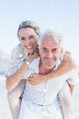 Man giving his smiling wife a piggy back at the beach against snow falling
