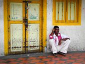 A man sitting on the main street in Little India.