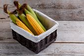 pic of corn-silk  - Basket of sweet corn on wooden background - JPG
