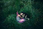 girl like a fairy sitting in grass meadow  hugs lost dog shot from above