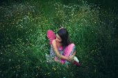girl like a fairy sitting in meadow grass with pink wings shot from above