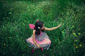 girl like a fairy sitting in meadow grass picking  a flower with pink wings shot from above