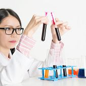 Asian lab worker doing blood test analysis, on plain background.