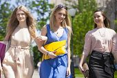 Three beautiful fashion women walking on the street in Moscow city