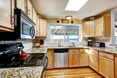 Bright Kitchen With Granite Tops And Black Appliances