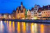 GDANSK, POLAND - 25 JULY 2014: Old town of Gdansk at night with reflection in Motlawa river. Gdansk is the historical capital of Polish Pomerania with medieval old town architecture.