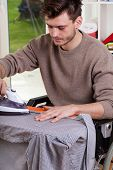 Man On Wheelchair Ironing Shirt