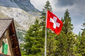 Swiss Flag - National Symbol Of Switzerland With Alps In Background