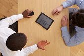 Overhead View Of Businesspeople With Digital Tablet At Desk