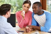 Worried Couple Talking With Financial Advisor In Office