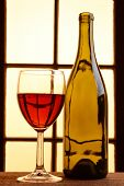 A wine still life with warm tones. One empty wine bottles and a glass of red wine in front of a window with warm sunlight.
