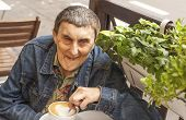 Elderly disabled man with cerebral palsy, smiling sitting at an outdoor cafe.