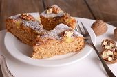 foto of cake stand  - Pieces of delicious cake with nuts on wooden stand on table close up - JPG