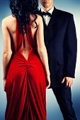 Beautiful young couple in love in evening dresses posing at studio. Fashion.