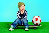 Cute two year boy sitting on a skateboard with a ball. Fashion. Childhood.