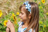 Beautiful little girl and sunflower