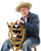 A senior adult cowboy sitting backwards on an old ladder-back chair.  On a white background.