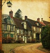 Gerberoy. Old street in medieval village, northern France. Photo in retro style. Paper texture.
