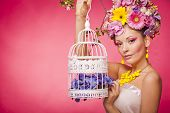 Healthy girl with a birdcage and flowers