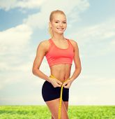 diet, sport, fitness and heath concept - smiling beautiful sporty woman with measuring tape