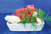fresh uncooked beef meat slices over white bowls ready to prepare with green hot peppers and greenery serving over blue wooden table