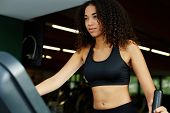 picture of time machine  - Beautiful afro american woman with curly hair exercising in gym on a step simulator machine beautiful and healthy woman enjoying time at gym - JPG