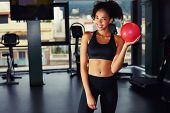Portrait of laughing woman standing with yoga ball at aerobics Pilates class