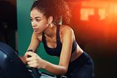 Shot of an attractive young woman at the gym riding on spinning bike with copy space
