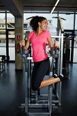 Full length portrait of happy fit woman exercising her abdominal muscles for beautiful figure