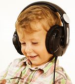 little cute boy in headphones listening music and smiling