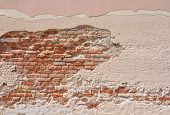 Aged and crumbling wall of brick and plaster