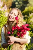 Happy young woman with magnificent blonde hair holding a bouquet of tulips. Countryside.