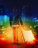 Young Man With Traveling Luggage Against  Lighting Of Urban Scene And Colorful Of City Life